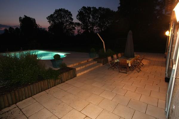 Tarrasse du gite autour de la piscine en nocturne